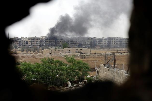 Un nuage de fumée s'élève du camp de réfugiés palestiniens de Yarmouk dans le sud de la capitale syrienne, après des bombardements du régime contre des positions du groupe Etat islamique (EI), le 29 avril 2018 [LOUAI BESHARA / AFP/Archives]