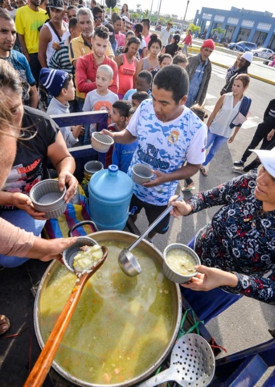 Distribution de soupe aux Vénézuéliens qui souhaitent émigrer vers le Pérou, à Tumbes, le 23 août 2018 [CRIS BOURONCLE / AFP]