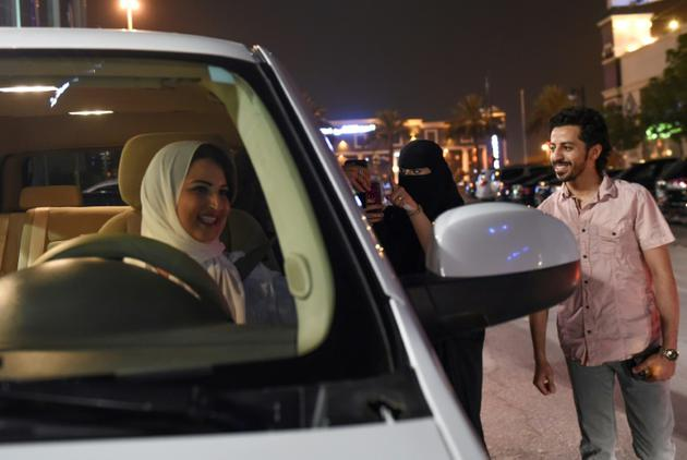 Une Saoudienne filme et apporte son soutien à Samar Al-Moqren (G) au volant de sa voiture à Ryad le 24 juin 2018, jour de la levée de l'interdiction aux femmes de conduire  [FAYEZ NURELDINE / AFP]