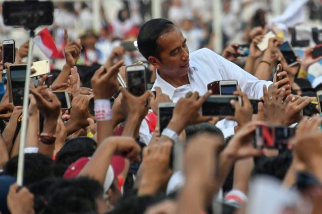 Le président Joko Widodo pose pour des selfies durant un meeting électoral à Jakarta le 13 avril 2019 [BAY ISMOYO / AFP/Archives]