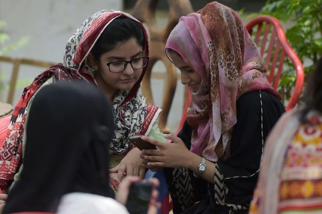 Des étudiantes utilisent leur smartphone sur le campus d'Islamabad le 12 juillet 2018 [Aamir QURESHI / AFP]