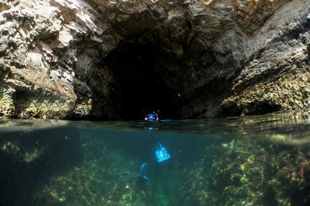 Un biologiste marin entre dans une grotte où viennent se reposer et se reproduire des phoques moines, les mammifères les plus en danger de Méditerranée. Photo prise le 23 mai 2018 [Emily IRVING-SWIFT / AFP]
