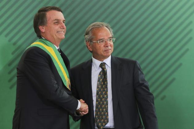 L'économiste ultra-libéral Paulo Guedes, ici le 1er janvier 2019 avec Jair Bolsonaro, est chargé du portefeuille de l'Economie [Sergio LIMA / AFP]