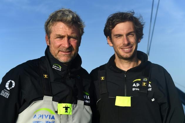 Yann Elies (g) and Charlie Dalin posent à bord de leur monocoque Apivia avant la Transat Jacques Vabre, le 10 octobre 2019 à Port-la-Forêt [Fred TANNEAU / AFP/Archives]