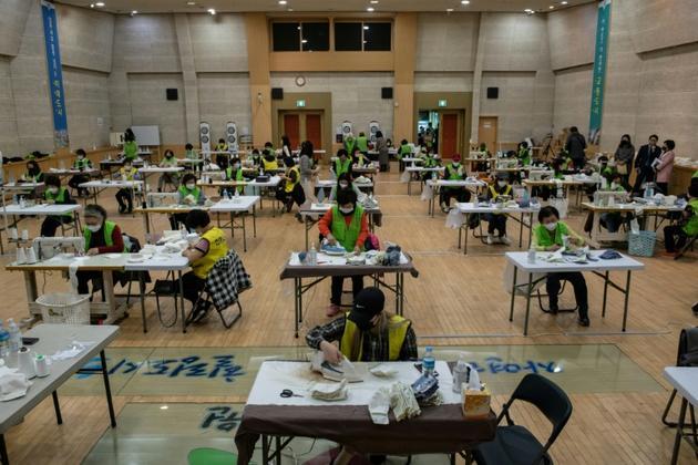 Des bénévoles fabriquent des masques à Séoul le 20 mars 2020 [Ed JONES / AFP]