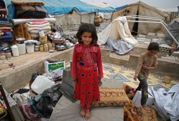 Une fillette syrienne se tient sur un matelas dans un camp pour personnes déplacées, dans le village d'Atmé (nord-ouest de la Syrie), le 1er mai 2019 [Aaref WATAD / AFP]