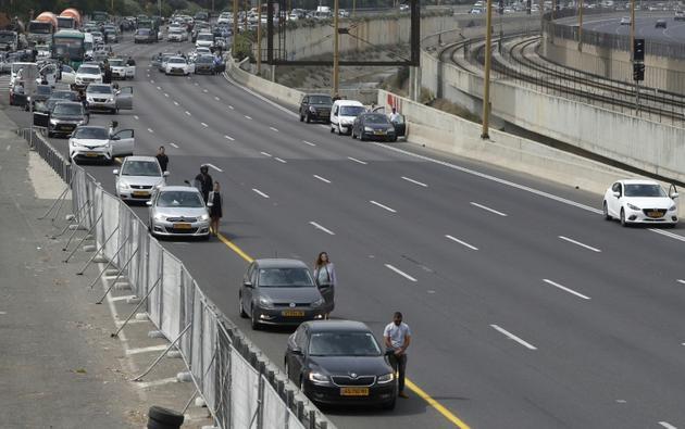 Les automobilistes sont descendus de leur voiture sur une autoroute de la ville israélienne de Tel-Aviv pour observer deux minutes de silence le 2 mai 2019 marquant la journée de la Shoah en mémoire des six millions de victimes juives du nazisme durant la Seconde Guerre mondiale [JACK GUEZ / AFP]