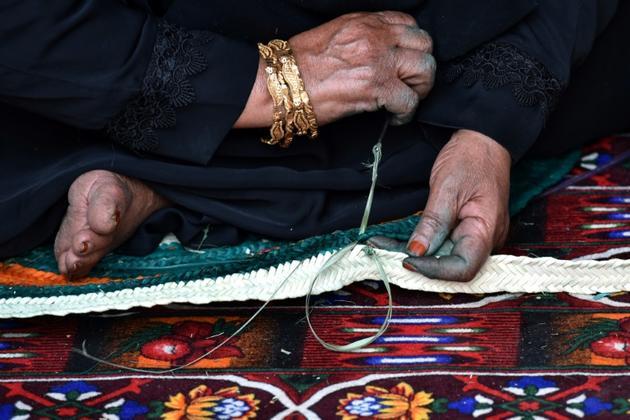 Une Saoudienne montre une façon de tisser les tapis à Al-Ula (Arabie saoudite), le 5 janvier 2019 [Fayez Nureldine / AFP]