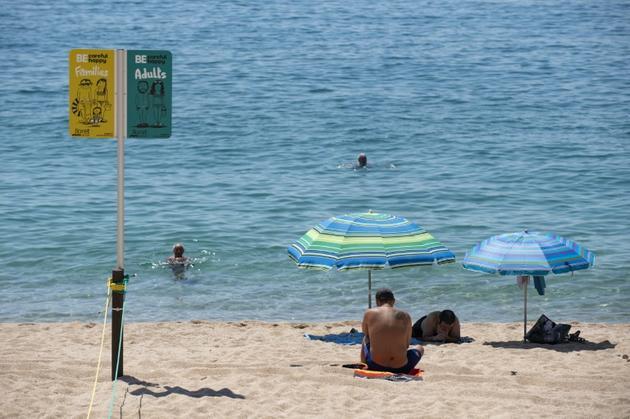 Un panneau indique les espaces réservés aux adultes et aux familles sur la plage de Lloret de Mar, le 22 juin 2020 en Espagne [Josep LAGO / AFP]
