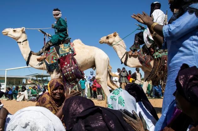 Des nomades défilent à dos de chameau pour le premier marathon du Niger, le 29 décembre 2019 à Agadez.<br />  [Nora Schweitzer / AFP]