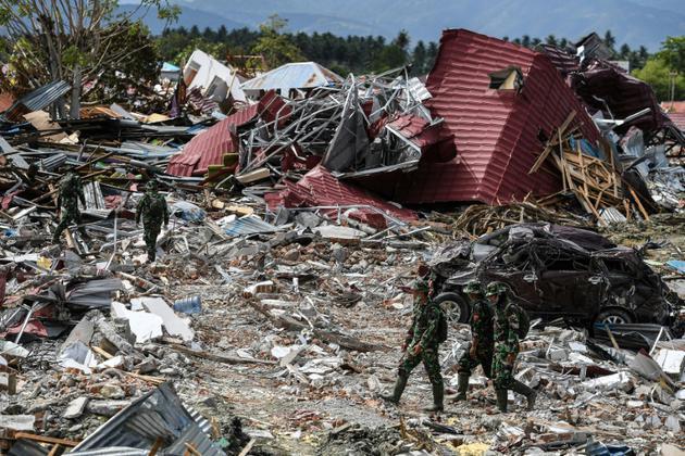 Des soldats recherchent des victimes dans les décombres de Petobo, le 8 octobre 2018 en Indonésie [MOHD RASFAN / AFP]