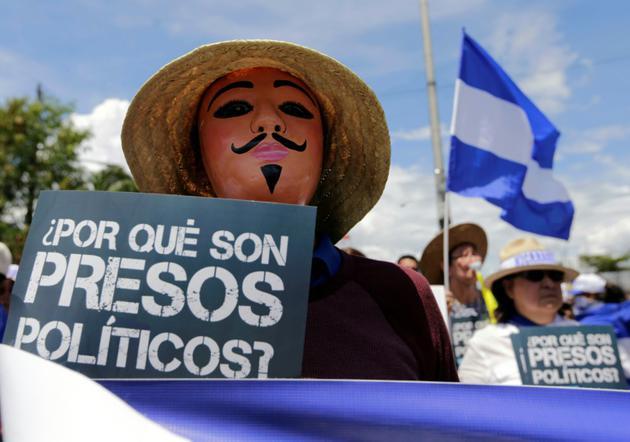 """Un manifestant anti-gouvernement brandit une pancarte """"Pourquoi sont-ils des prisonniers politiques ?"""" lors d'une marche réclamant la libération de prisonniers politiques à Managua, le 15 août 2018 [INTI OCON / AFP]"""