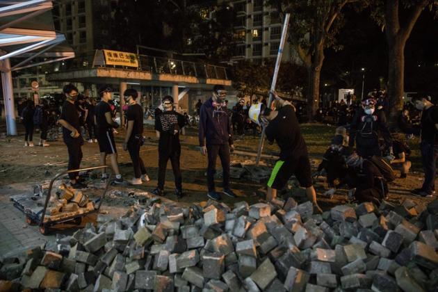 Des manifestants rassemblent des pavés devant l'Université chinoise de Hong Kong, le 12 novembre 2019 [DALE DE LA REY / AFP]