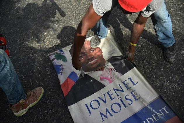 Un manifestant découpe un portrait du président haïtien Jovenel Moise, le 7 juillet 2018 à Port-au-Prince [HECTOR RETAMAL / AFP/Archives]