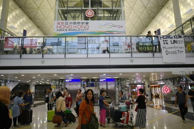 Arrivée des voyageurs à l'aéroport international de Hong Kong le 12 août 2019, alors que des manifestants prodémocratie ont investi les lieux  [Manan VATSYAYANA / AFP]