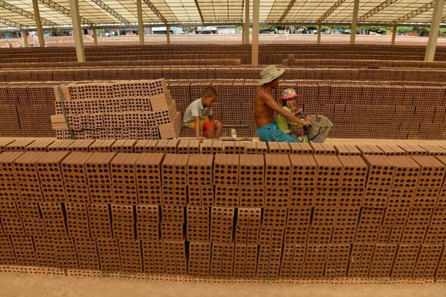Des Cambodgiens travaillent dans une manufacture de briques près de Phnom Penh, le 11 décembre 2018 [TANG CHHIN Sothy / AFP]
