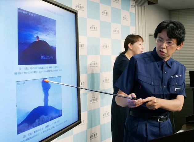 Un scientifique de l'agence météorologique japonaise montre le mont Asama en éruption lors d'une conférence de presse, le 8 août 2019 à Tokyo [JIJI PRESS / JIJI PRESS/AFP]