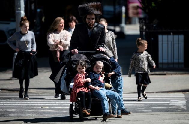 Un homme traverse une rue avec ses enfants, dans le quartier de Williamsburg Brooklyn à New York, qui compte une importante population juive orthodoxe, le 24 avril 2019 [Johannes EISELE / AFP]