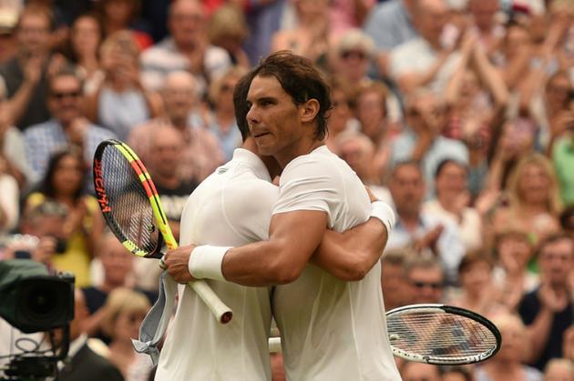 Rafael Nadal (d) donne l'accolade à Novak Djokovic après leur demi-finale de Wimbledon, le 14 juillet 2018 [Oli SCARFF                           / AFP]