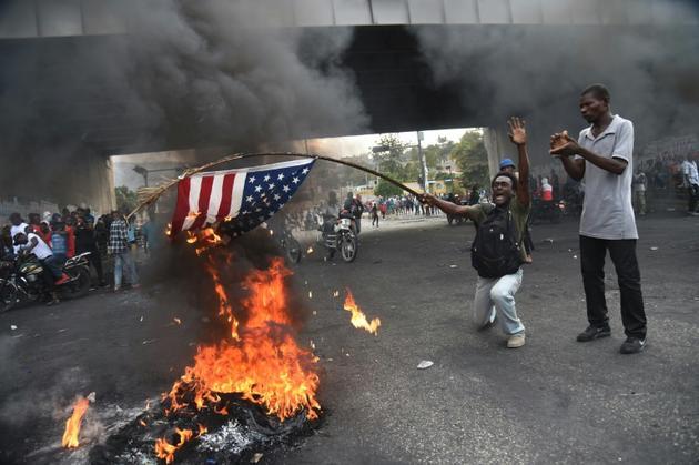 Des manifestants brûlent un drapeau américain, le 15 février 2019 à Port-au-Prince, en Haïti [HECTOR RETAMAL / AFP]