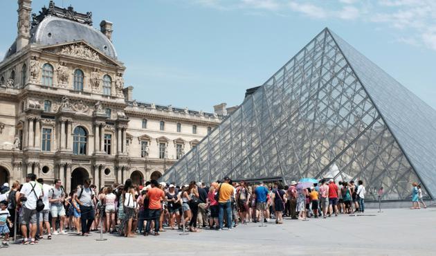 Touristes faisant la queue pour entrer au Louvre, à Paris, le 2 juillet 2015 [MIGUEL MEDINA / AFP/Archives]