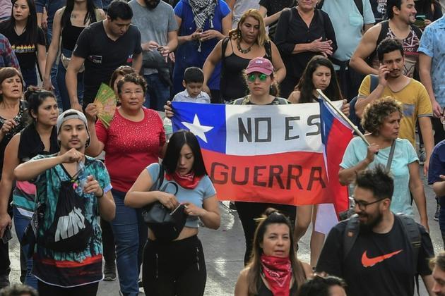 Manifestants brandissant le drapeau chilien à Santiago le 25 octobre 2019<br />  [Martin BERNETTI / AFP]