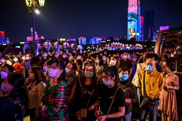 Des passagers portant des masques pour éviter de propager le coronavirus attendent d'embarquer dans un bateau pour regarder un spectacle, à Wuhan le 27 septembre 2020  [Hector RETAMAL / AFP/Archives]