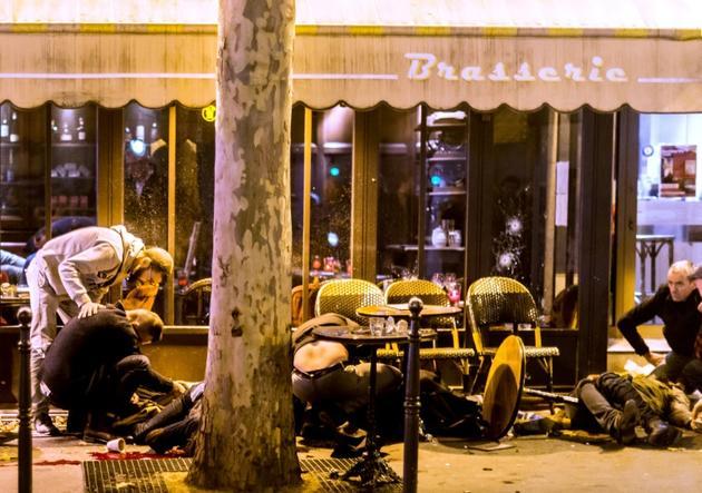 Des victimes des attentats du 13 novembre 2015, à Paris, devant la terrasse du café Bonne Bière [ANTHONY DORFMANN / AFP/Archives]