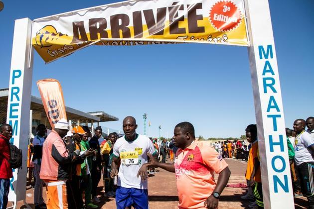 Un des participants au Grand Marathon du Ténéré franchit la ligne d'arrivée le 29 décembre 2019 à Agadez, dans le nord du Niger.<br />  [Nora Schweitzer / AFP]