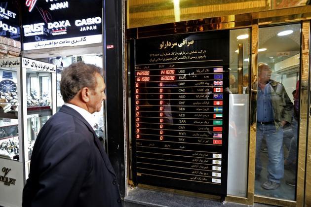 Un homme regarde un panneau affichant les taux de change des devises étrangères. Le rial iranien a perdu une grande partie de sa valeur depuis le rétablissement des sanctions américaines contre l'Iran. Photo du 3 novembre 2018 à Téhéran [ATTA KENARE / AFP]