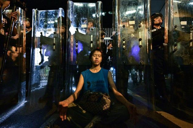 Une femme médite devant les forces de l'ordre, le 12 juin 2019 à Hong Kong [Anthony WALLACE / AFP]