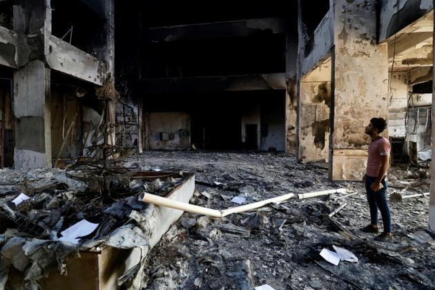 Un homme au milieu des décombres du siège du gouvernorat provincial détruit par les flammes le 7 septembre 2018  [Haidar MOHAMMED ALI / AFP]