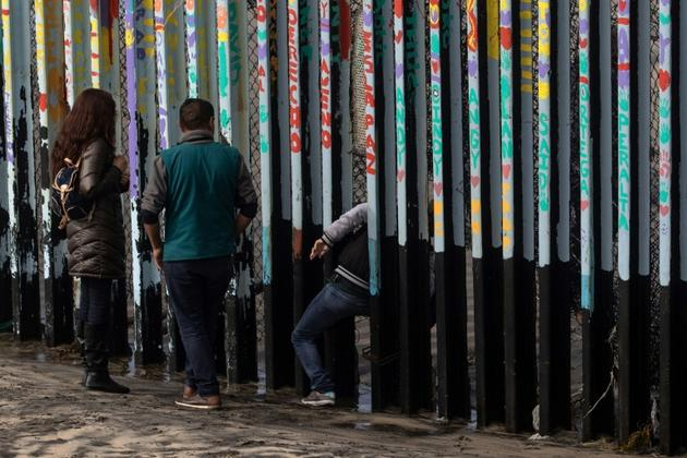Une personne se glisse à travers les barres métalliques marquant la frontière entre Etats-Unis et Mexique, le 18 janvier 2019 à Tijuana [Guillermo Arias / AFP]