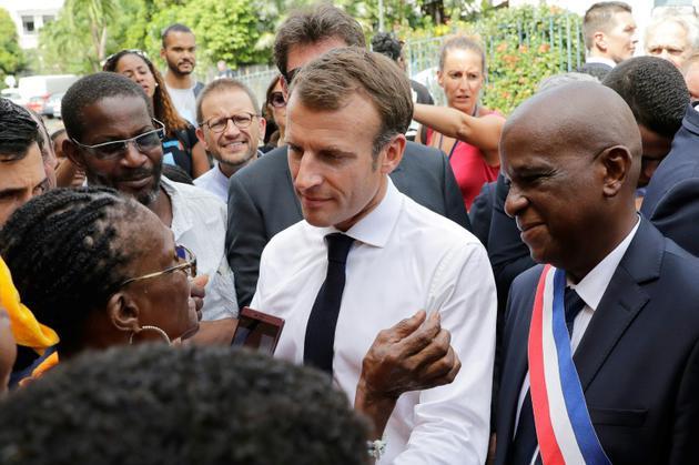 Le président Emmanuel Macron écoute une habitante de Saint-Pierre, en Martinique, le 27 septembre 2018 lors de son déplacement aux Antilles [Thomas SAMSON / POOL/AFP]