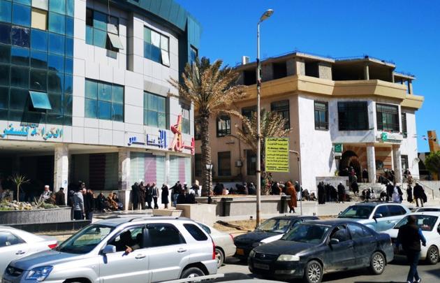 Des Libyens font la queue devant une banque dans le centre de Tripoli, le 8 avril 2019 [Imed LAMLOUM / AFP]