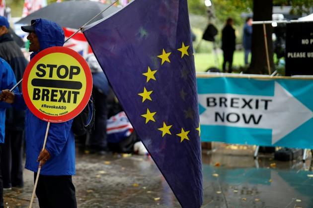 Un manifestant anti-Brexit porte un panneau et un drapeau européen devant le Parlement britannique à Londres, le 17 octobre 2019 [Tolga Akmen / AFP]