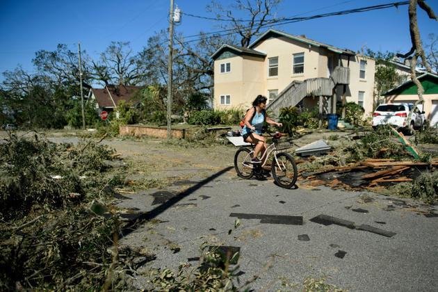 Une femme à vélo dans les rues de Panama city (Floride), après le passage de l'ouragan Michael le 11 octobre 2018. [Brendan Smialowski / AFP]