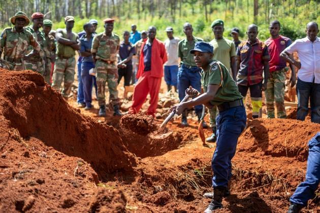Un policier creuse une tombe collective, le 22 mars 2019 à Chimanimani, au Zimbabwe, le 22 mars 2019 [Zinyange AUNTONY / AFP]