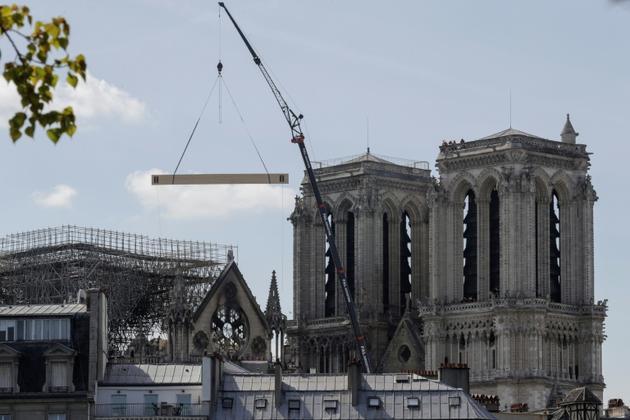 Une grue soulève des matériaux de construction pour consolider Notre-Dame le 17 avril 2019, deux jours après l'incendie [Thomas SAMSON / AFP]