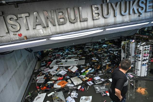 Un commerçant tente de sauver sa marchandise dans un centre commercial du quartier d'Eminonu à Istanbul, le 17 août 2019. [Ozan KOSE / AFP]