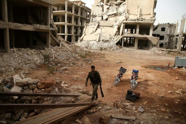 Un rebelle syrien au milieu de destructions dans le secteur d'al-Rachidine dans l'ouest de la province d'Alep près de la province d'Idleb, dans le nord de la Syrie, le 15 octobre 2018 [Aaref WATAD / AFP]