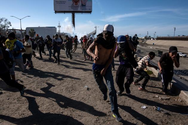 Des migrants centraméricains s'enfuient après des tirs de gaz lacrymogène par les forces de l'ordre américaines, près de la frontière entre le Mexique et les Etats-Unis à Tijuana, le 25 novembre 2018 [GUILLERMO ARIAS / AFP]