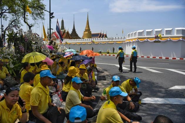 Des Thaïlandais attendent près du Grand palais le passage de la grande parade pour le couronnement du roi Maha Vajiralongkorn dans les rues de Bangkok, le 5 mai 2019 [Lillian SUWANRUMPHA / AFP]