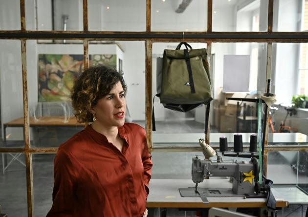 Vera Guenther, co-fondatrice de mimycri, dans son atelier à Berlin, un des sacs réalisés à partir de canot de sauvetage derrière elle [Tobias SCHWARZ / AFP]