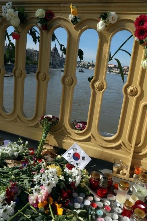 Photo prise le 1er juin 2019 à Budapest, montrant des fleurs, des bougies et un drapeau sud-coréen sur le pont Marguerite qui enjambe le Danube, au-dessus du lieu de la collision entre un bateau de croisière et une embarcation de touristes, qui a fait 7 morts et 21 disparus, principalement des Sud-Coréens. [FERENC ISZA / AFP]