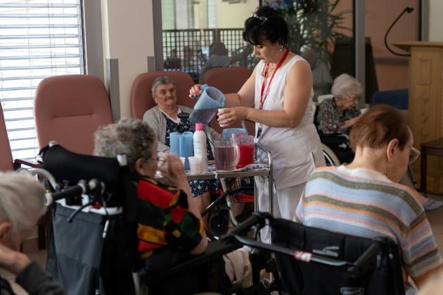 Une aide-soignante sert des rafraîchissements aux pensionnaires d'une maison de retraite à Souffelweyersheim, dans l'Est de la France, le 24 juin 2019 [PATRICK HERTZOG / AFP]