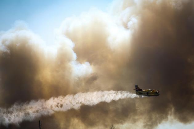 Un avion bombardier d'eau effectue un largage sur les feux de forêt près de Monchique, dans la région de l'Algarve, sud du Portugal, le 8 août 2018<br /> [CARLOS COSTA / AFP]