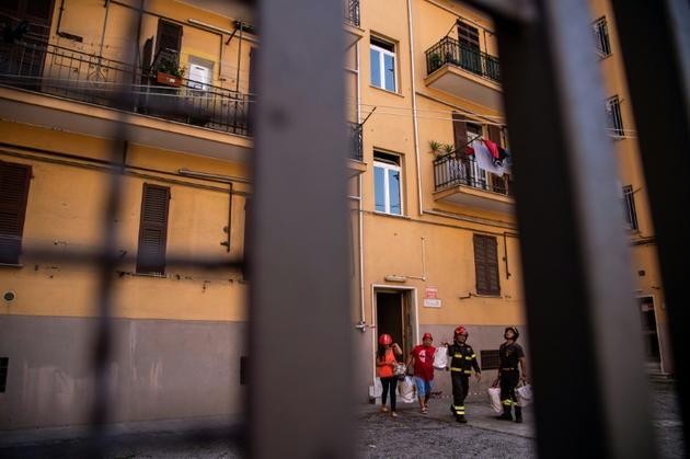 """Des habitants quittent leurs maisons de la rue Fillak, dans la """"zone rouge"""" situéée sous les restes du Pont Morandi, à Gênes (Ligurie), le 16 août 2018 [MARCO BERTORELLO / AFP/Archives]"""