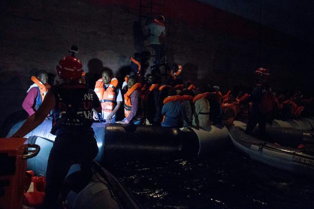 Photo prise le 22 juin 2018 au large des côtes libyennes et fournie par l'ONG Mission Lifeline montrant des migrants secourus embarquant à bord du porte-conteneurs Maersk [Danilo CAMPAILLA / Mission Lifeline e. V./AFP]