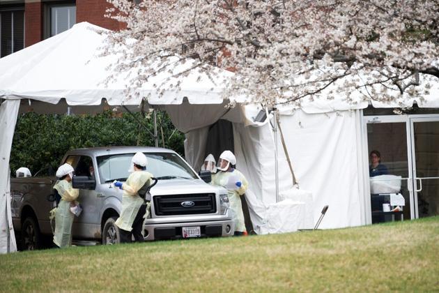Du personnel médical teste dans les voitures les personnes, sur le parking de l'hôpital John Hopkins à Baltimore, le 19 mars 2020 [JIM WATSON / AFP]